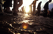 Festival-goers trudging through a muddy field, Glastonbury, 2000's