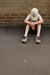 Boy sitting by side of wall with his head bowed,