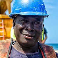 Un obrero de Angola, después de terminar su trabajo en un muelle en un puerto, está listo para comenzar una nueva asignación. La Guaira. Venezuela. A worker from Angola, after completing his work on a dock at a port, is ready to start a new assignment. La Guaira. Venezuela.