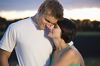 Couple stand embracing with eyes closed in evening light