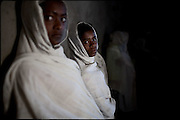 """Women, in a Orthodox Church, during the Sunday function. North West of Ethiopia, on sunday, Febrary 15 2009.....In a tangled mingling of tradition and culture, in the normal place of living, in a laid-back attitude. The background of Ethiopia's """"child brides"""", a country which has the distinction of having highest percentage in the practice of early marriages despite having a law that establishes 18 years as minimum age to get married. Celebrations that last days, their minds clouded by girls cups of tella and the unknown for the future. White bridal veil frame their faces expressive of small defenseless creatures, who at the age ranging from three to twelve years shall be given to young brides men adults already...To protect the identities of the recorded subjects names and specific places are fictional."""