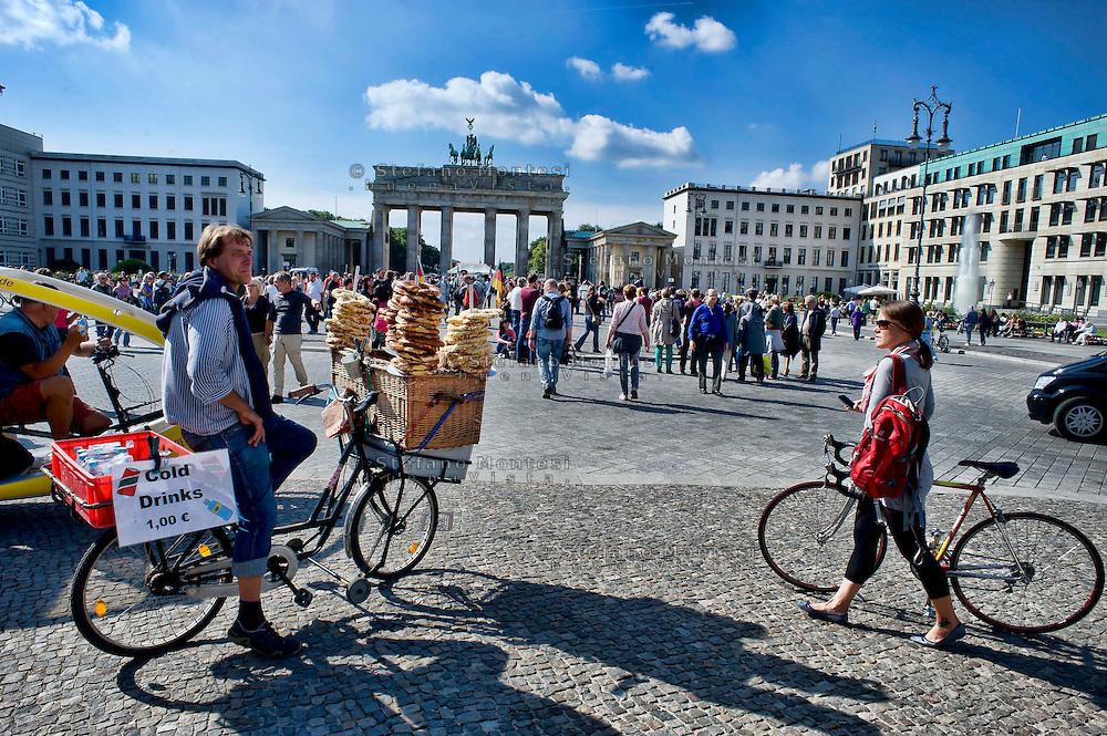 Berlino 14  Settembre 2013<br /> Un venditore di bretzel,classico pane tedesco, in  Pariser Platz con lo sfondo dellla Porta di Brandenburg.<br /> A seller of  bretzel, classic German bread, at Pariser Platz, with the background of the Brandenburg Gate. --