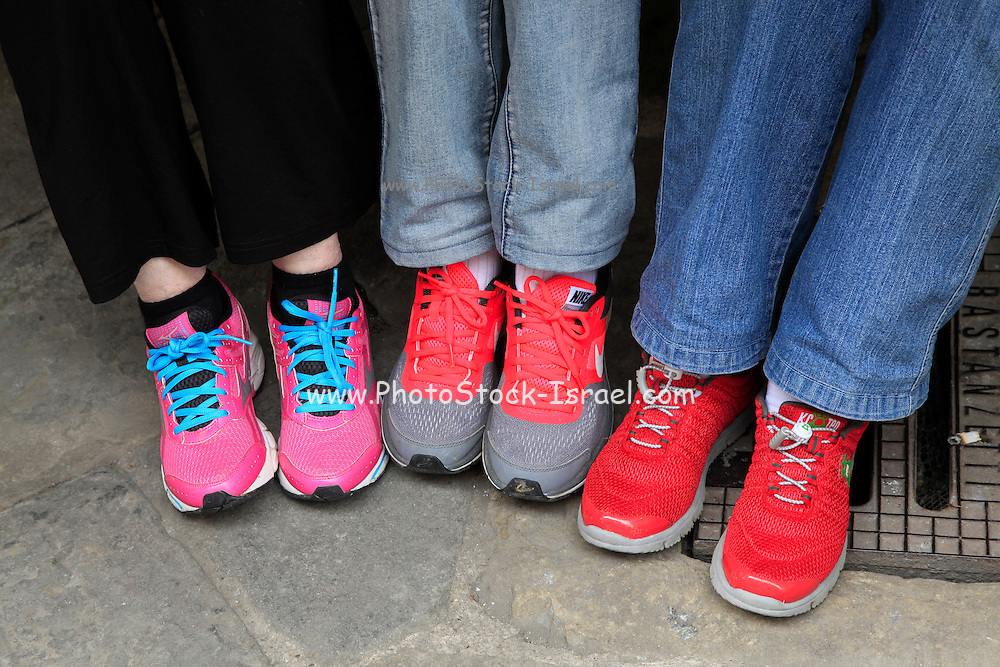 Feet and legs of three women wearing jeans and trainers