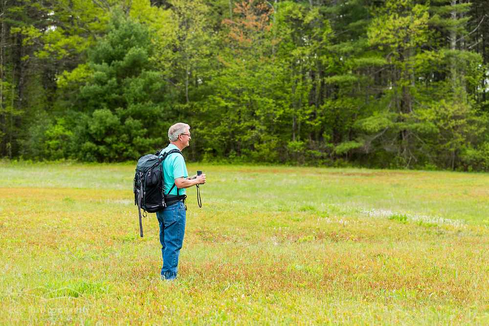 A man birdwatching in a field in York, Maine.