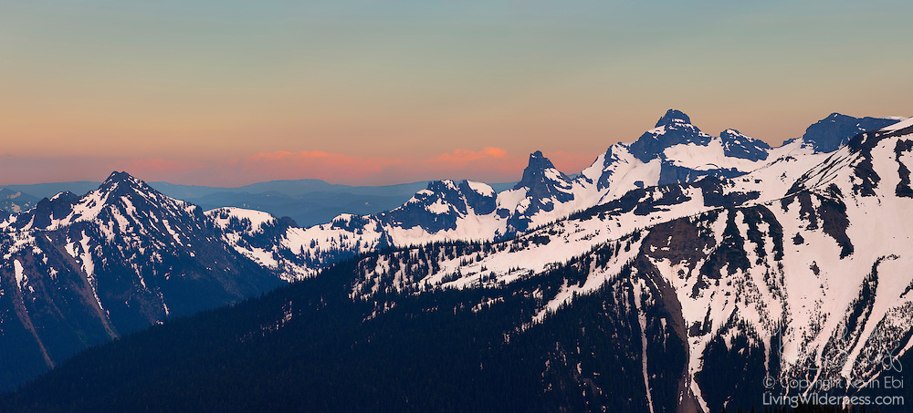 The Cowlitz Chimneys, visible in the right third of this panorama, are remnants of a rhyolite plug on the east slope of Mount Rainier. The Cowlitz Chimneys, which are part of the Cascade Range, range in height from 7,015 to 7,605 feet (2,138 to 2,318 meters).
