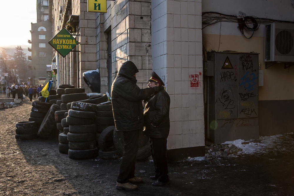 KIEV, UKRAINE - JANUARY 24: An anti-government protesters helps another adjust his coat to fight off the cold on January 24, 2014 in Kiev, Ukraine. After two months of primarily peaceful anti-government protests in the city center, new laws meant to end the protest movement have sparked violent clashes in recent days. (Photo by Brendan Hoffman/Getty Images) *** Local Caption ***