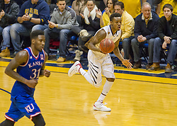 West Virginia Mountaineers guard Daxter Miles Jr. (4) dribbles the ball up the floor against the Kansas Jayhawks during the second half at the WVU Coliseum.