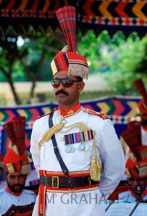 Military man with medals standing at ease watching a parade in Pakistan