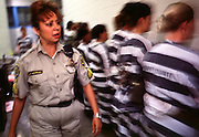 """01 NOVEMBER 1999  - PHOENIX, ARIZONA, USA: A detention officer in the Maricopa Country Jail in Phoenix, AZ, inspects women prisoners who are on the county's chain gang before taking them out on the streets to perform public service clean up. Maricopa county sheriff Joe Arpaio claims to have the only women's chain gang in the United States. He has been criticized for the chain gang but claims to be an """"equal opportunity incarcerator."""" He has said that if puts men on a chain gang he will also put women on a chain gang. © Jack Kurtz  WOMEN   PRISON   CIVIL RIGHTS  SOCIAL ISSUES"""