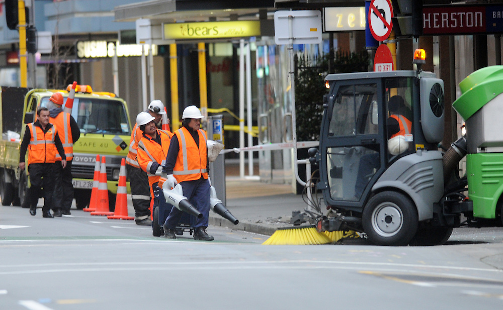 Council staff begin the clean up of broken glass on Featherston Street following the 6.6 earthquake that shock the capital Sunday, Wellington, New Zealand, Monday, July 22, 2013. Credit:SNPA / Ross Setford