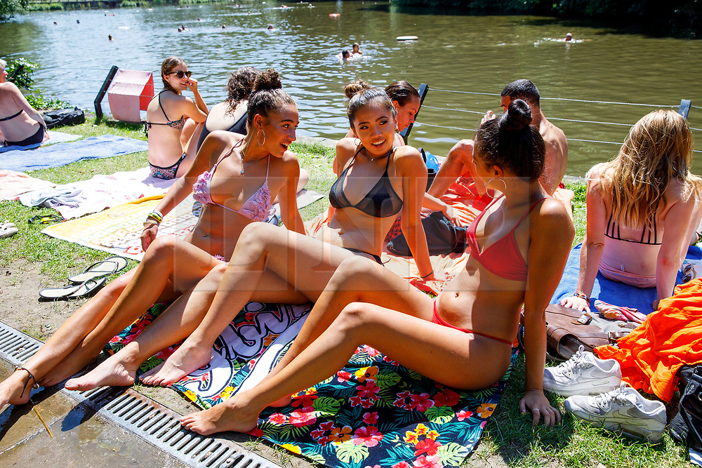 © Licensed to London News Pictures. 05/07/2017. London, UK. Lois Dean, Lily Wickens and Clare Arkin sunbathe in Hampstead Heath Mixed Bathing Pond in north London as temperatures hit 28C degrees on 5 July 2017. Photo credit: Tolga Akmen/LNP