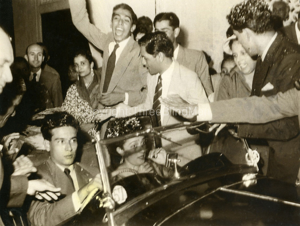 Vernon &amp; Marlene Tissera leave on their honeymoon from the reception held at the Women's International Club on Guildford Crescent. In the background looking towards camera is John Rodie, Marlene's uncle.Gwen Philips in a sari, and next to her with a raised hand is Alan PANAMBALANA, with striped tie is Ralph Nell, and half covered behind him is Tissa Atapattu. With his head covered in confetti is Sally Atapattu, the Best man.  Next to him, wearing a hat, is Mrs. Krasse, the brides Mother. The car is an MG TD.<br /> 10th of August 1957