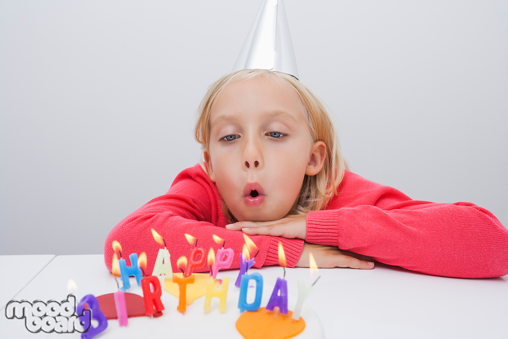 Girl blowing birthday candles at table in house