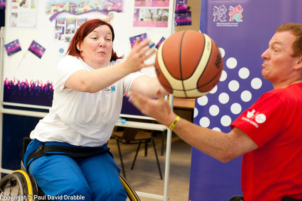 Cadbury 2012 Paralympic demonstration Sheffield..Kathryn Betts (London 2012 Site Ambassador for Sheffield) tries her hand at wheelchair basketball alongside coach Andy Atkinson who was on site with the  RGK Rhinos Sporting club wheelchair basketball team to give Sheffield colleagues an insight into Wheelchair basketball, Paralympic sports and promote awareness around the different sporting disciplines.   .  ....3 September 2012.Image © Paul David Drabble