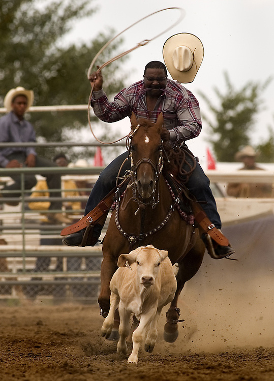 "The Bill Pickett Rodeo, based in Denver, Colorado, is the only all-black invitational rodeo in America.  Black cowboys compete seasonally for points toward the best-all-around cowboy at rodeo events in major U.S. cities.  ..Contact Larry Price for specific info on individual images....wikipedia.org article on Bill Pickett:..Bill Pickett was born near Taylor, Texas in 1870. He was later called the ""Greatest Cowboy"" of his day. Bill Pickett was one of five boys among the Picketts' thirteen children. Bill left school in the 5th grade to become a ranch hand, and soon he began to ride horses and watch the long horn steers of his native Texas. It was known among cattlemen that, with the help of a trained bulldog, a stray steer. Bill Pickett had seen this happen on many occasions. He also thought that if a bulldog could do this feat, so could he. Bill Pickett practiced his stunt by riding hard and springing from his horse and wrestling the steer to the ground. Bill Pickett soon became known for his tricks and stunts at local country fairs. With his four brothers, he established The Pickett Brothers Bronco Busters and Rough Riders Association. The name of Bill Pickett soon became synonymous with successful Rodeos. He did his Bull-Dogging act, traveling about in Texas, Arizona, Wyoming and Oklahoma. In 1905 he joined the 101 Wild West Shows as they traveled across the country and in Canada, South America, and even Great Britain. In 1921, he appeared in the films, The Bull Dogger and The Crimson Skull...In 1932, after he retired from the Wild West Shows, Bill Pickett was killed when he was kicked in the head by a wild bronco. In 1971 Bill Pickett was inducted into the National Rodeo Cowboy Hall of Fame.[3]"