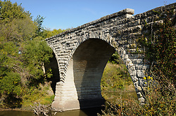 The abandoned Clements Stone Arch Bridge over the Cottonwood River is located in the Kansas Flint Hills approximately 1/2 mile south of Clements, south of highway US 50 near the Flying W Ranch in Chase County. The bridge with its massive 28 foot double arches is the largest and one of the oldest limestone bridges in Kansas. Built in 1886 though not completed until 1888, the bridge was placed on the National Register of Historic Places in 1976. Today, the bridge no longer carries traffic and seems out of place now that the road over the bridge ends up into a pasture.