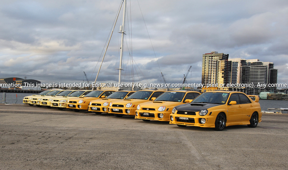 Subaru Impreza WRX Club Spec Evo 4 & 5 Group Shoot.Docklands, Port Melbourne, Victoria.24th March 2005.The Impreza WRX Limited Edition Club Spec Evo 4. Just 300 of these special editions were be sold in Australia: 250 sedans and 50 hatches. Sporting a rare yellow colour scheme, the Club Spec Evo 4 includes a broad range of value-added features. And each car is individually numbered, further enhancing its special appeal. The Club Spec Evo 4 featuress black alloy wheels, a Momo airbag steering wheel, STi type metal finished instruments, an AM/FM radio with CD player and tweeter speakers in the front door handles. And of course there is limited edition badging on the rear doors and boot lid. In the sedan, yellow trim inserts also highlight the seats..Subaru Impreza WRX Club Spec Evo 5, featuring an eye-catching orange paint scheme and extra features. The Club Spec EVO 5 includes a full electric factory-fitted sunroof,  the first time this option has been available on any model Impreza WRX. It also got a 2DIN AM/FM radio cassette with six-stack in-dash CD changer. Special decals and badging are featured outside, while each model is individually numbered on the centre console.Just 140 Impreza WRX Evo 5 sedans and 60 hatches will be sold, all with manual transmissions..(C) Joel Strickland Photographics.Use information: This image is intended for Editorial use only (e.g. news or commentary, print or electronic). Any commercial or promotional use requires additional clearance.