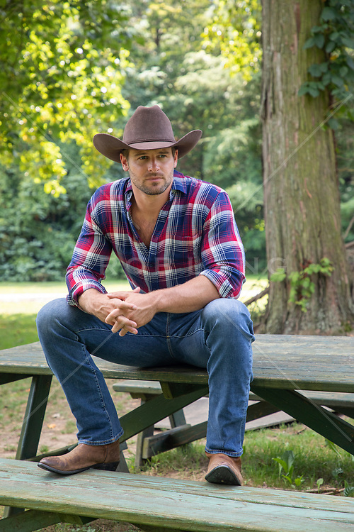 hot cowboy sitting on a picnic table