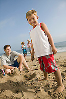 Boy Playing in Sand with Family at Beach
