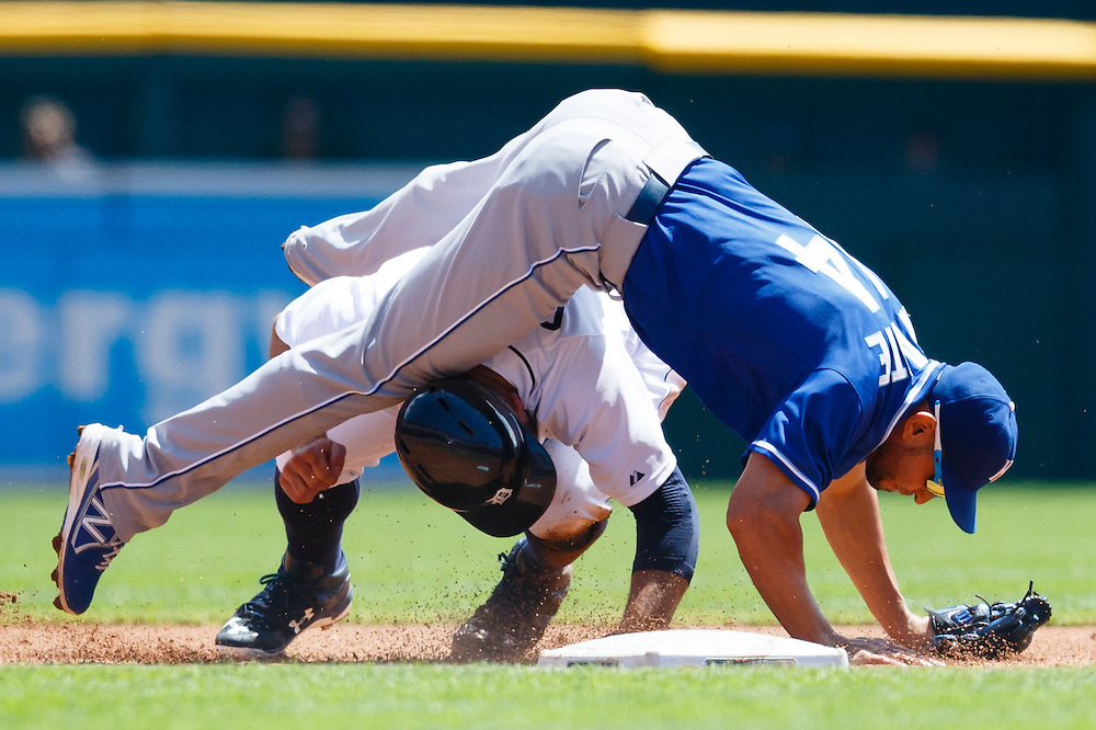 Aug 6, 2015; Detroit, MI, USA; Kansas City Royals second baseman Omar Infante (14) falls over Detroit Tigers left fielder Tyler Collins (18) after makes a throw to complete a double play in the second inning at Comerica Park. Mandatory Credit: Rick Osentoski-USA TODAY Sports