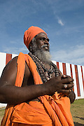 Swami in robes at the annual Nallur festival. Jaffna Peninsula. ..Wall of the Nallur Hindu Kovil in the background...2004 July.