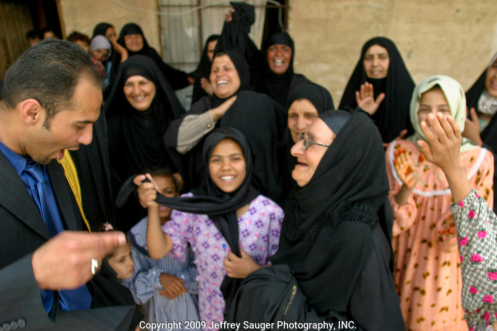 """Emad Al-Kasid dances to a chorus of """"Welcome, welcome, this the day you return,"""" sing women belonging to Al Hacham tribe and the Al-kasid family during the Al-kasid family's Istikbal, or homecoming, in their home village Suq ash Shuyukh about 20 miles southeast of Nasiriyah, Iraq, Tuesday, July 29, 2003...The women spend most of their time making dough, baking bread, milking cows, taking care of children, preparing food, etc. as the men gather outside the family complex...The Al-kasid family fled Iraq after the Gulf War and their part in the uprising against Saddam Hussein in 1991, spent 3 years in Rafa, Saudi Arabia and finally settled in Dearborn, MI. The family hasn't been home to Iraq in 13 years."""