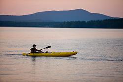 A kayaker on Umbagog Lake at Umbagog Lake State Park, Cambridge, New Hampshire.