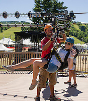 Mike Infantino disconnects Nicquelle Timson's harness after completing the practice zip at the base of Gunstock Mountain.   (Karen Bobotas/for the Laconia Daily Sun)