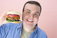 Overweight mid-adult man holding hamburger