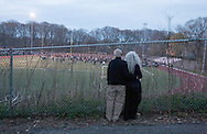 A couple watch through the fence at Jonathan Law High School during a vigil for slain student Maren Sanchez in Milford, Connecticut April 28, 2014. Sanchez, 16 was killed on Friday in a stairwell at the school by a classmate who may have been upset that she rebuffed his invitation to the prom, police said. The prom was postponed after the incident. REUTERS/Michelle McLoughlin (UNITED STATES - Tags: CRIME LAW EDUCATION)