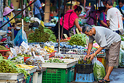 "26 SEPTEMBER 2012 - BANGKOK, THAILAND:  A man shops for produce in Klong Toey Market in Bangkok. Klong Toey (also called Khlong Toei) Market is one of the largest ""wet markets"" in Thailand. The market is located in the midst of one of Bangkok's largest slum areas and close to the city's original deep water port. Thousands of people live in the neighboring slum area. Thousands more shop in the sprawling market for fresh fruits and vegetables as well meat, fish and poultry.    PHOTO BY JACK KURTZ"