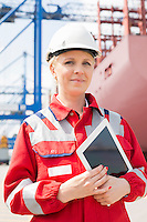 Portrait of confident female engineer holding tablet computer in shipping yard