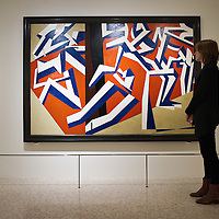 """VENICE, ITALY - JANUARY 28: A member of staff of the Guggenheim Museum admires the painting by David Bomberg """"The Mud Bath """" at the press launch of the Vorticist exhibition on January 28, 2011 in Venice, Italy. The Vorticists: Rebel Artists in London and New York, 1914-1918, is the first exhibition devoted to Vorticism to be presented in Italy will be open at the Peggy Guggenheim Collection from  January 29 through May 15, 2011."""