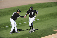 CHICAGO - SEPTEMBER 12:  Andruw Jones #25 is greeted by third base coach Jeff Cox #8 of the Chicago White Sox after Jones hit a grand slam home run on September 12, 2010 at U.S. Cellular Field in Chicago, Illinois.  The White Sox defeated the Royals 12-6.  (Photo by Ron Vesely)
