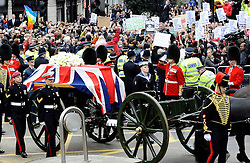 Protestors turn their back on the the coffin of Margaret Thatcher as it travels past Ludgate Circus during the funeral of Baroness Margaret Thatcher, London, UK, Wednesday 17 April, 2013, Photo by: i-Images