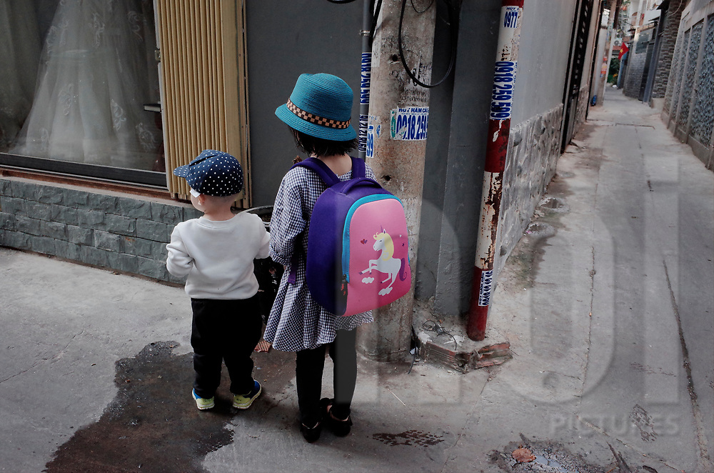 Two young Vietnamese kids wander in a narrow alleyway of Ho Chi Minh City, Vietnam, Southeast Asia