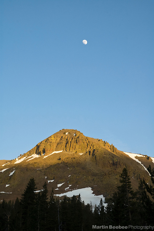 The moon rises over an unnamed peak touched by alpenglow in the Eastern Sierra Nevada, Toiyabe National Forest, California