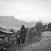 A Bhutanese man with his son walking through an unpaved road of Gangtey valley, Bhutan, Asia