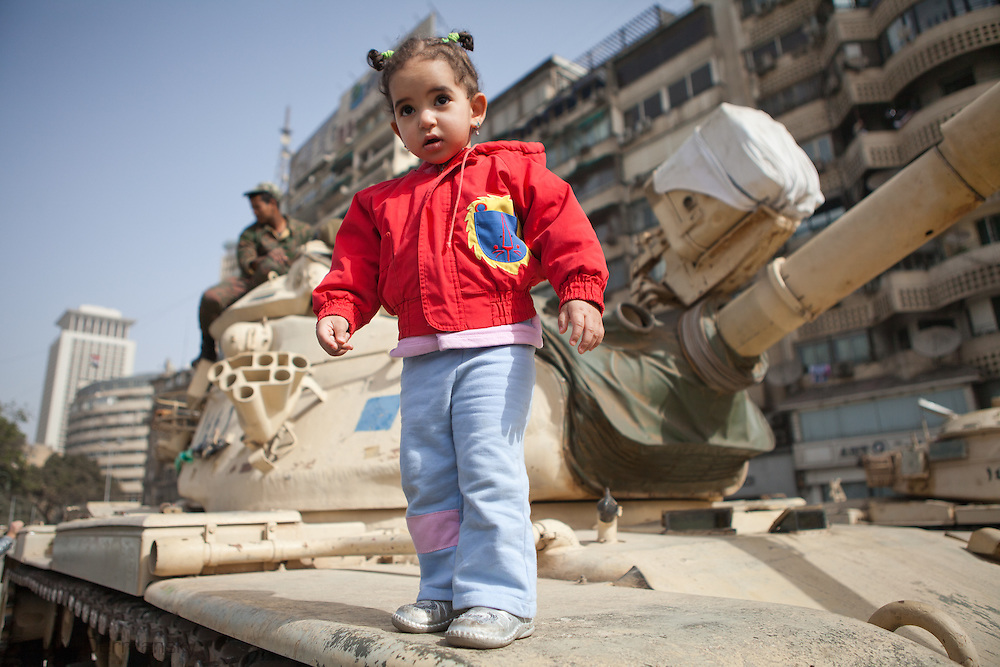 Young girl posing for a photo on a Egyptian Tank near the National TV building in Cairo. After Mubarak was forced to step down by protestors after an 18 day revolution, tanks deployed to protect the city became backdrops for family photos. The Egyptian Military took control of Egypt when Mubarak was forced from office during the January 25th revolution.