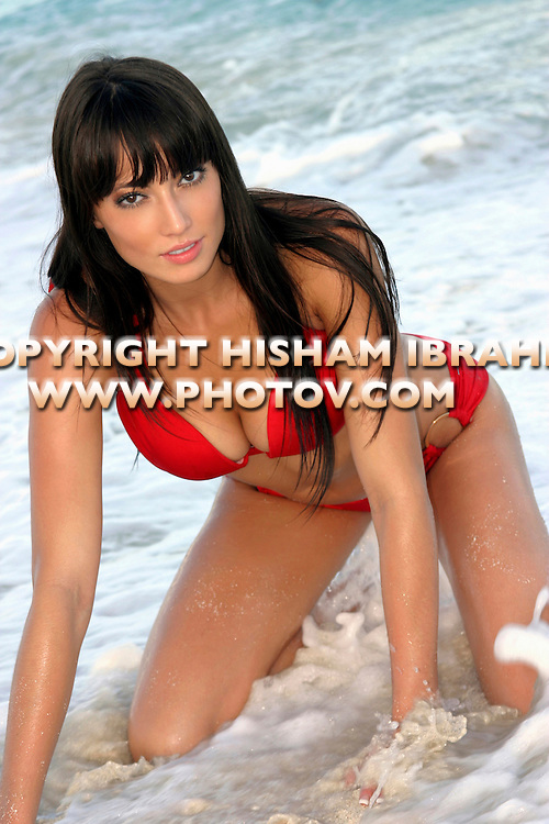 Beautiful young brunette woman in Red Bikini on beach.