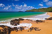 Surf, sand and blue green waters at Secret Beach (Kauapea Beach), Kilauea Lighthouse visible, Kauai, Hawaii USA
