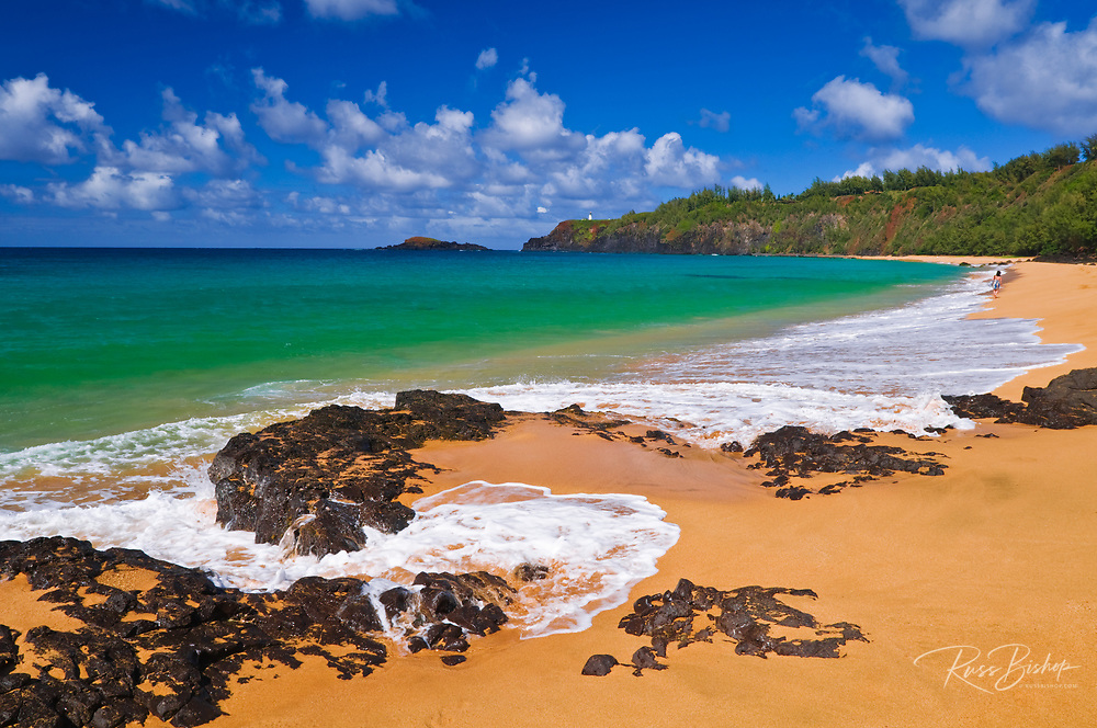 Surf, sand and blue green waters at Secret Beach (Kauapea Beach), Kilauea Lighthouse visible, Island of Kauai, Hawaii USA