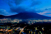 Aerial view of Antigua, Ciudad Vieja and nearby towns in Guatemala at sunset with street lights on, taken on Tuesday, Sept. 18, 2018. Dormant volcano Agua is in the background.