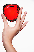 Woman holding up heart-shaped jewel between finger and thumb close-up of hand