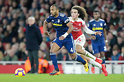 Fulham defender Denis Odoi (4) holds off Arsenal midfielder Matteo Guendouzi (29) as the Fulham manager Claudio Ranieri looks on in the distance during the Premier League match between Arsenal and Fulham at the Emirates Stadium, London, England on 1 January 2019.