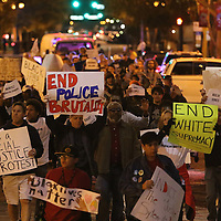 """Protesters march through downtown streets on the way to the Amway Arena, home of the Orlando Magic, to perform a """"die in"""" to rally against police brutality on Wednesday, December 10, 2014 in Orlando, Florida.  Since a Staten Island grand jury decided last week not to bring any charges against a white officer who was seen on video using a chokehold on Eric Garner, and other use of questionable force issues by the police across the country, the Orlando protesters wanted to represent the city of Orlando. (AP Photo/Alex Menendez)"""