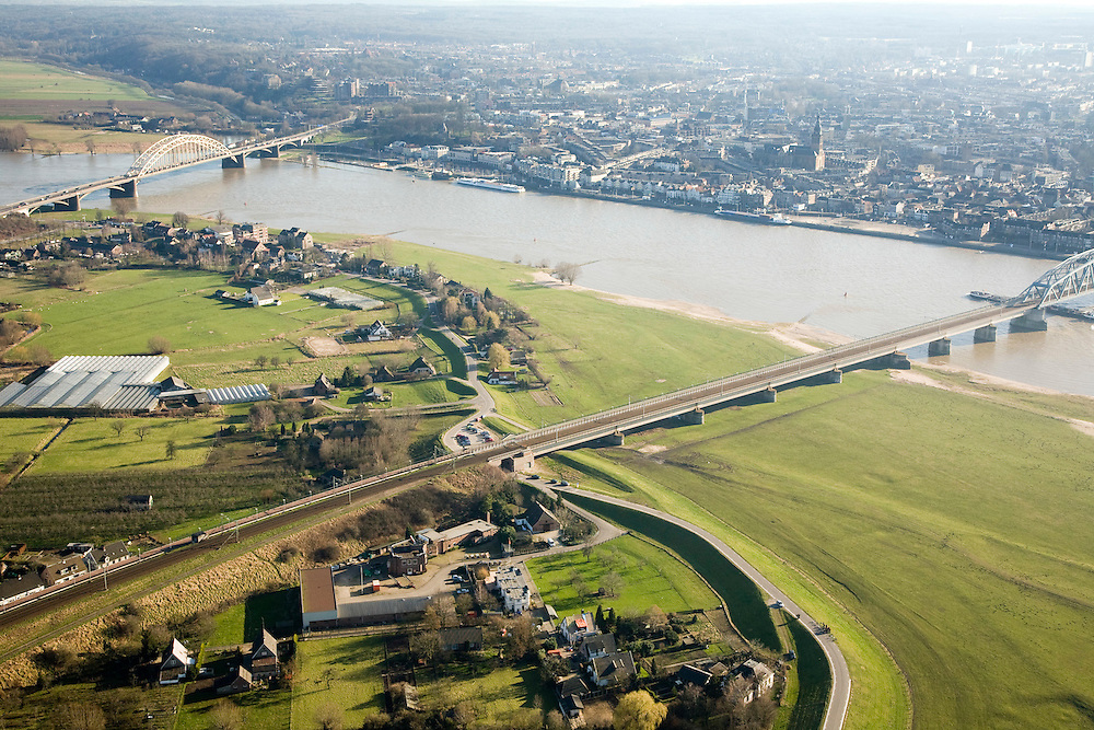 Nederland, Gelderland, Nijmegen, 11-02-2008; Waalsprong: aan de noordoever van de Waal, rond het dorp Lent zal een nieuw stadsdeel gebouwd gaan worden; ook wordt op deze lokatie een geul uitgegraven, meer landinwaarts, links van de dijk, om de rivier meer de ruimte te geven, Lent (aan de dijk) komt dan op een eiland te liggen; binnenstad Nijmegen aan de andere zijde van de rivier, Waalbrug in de verte, spoorbrug in de voorgrond; geul, rivier..luchtfoto (toeslag); aerial photo (additional fee required); .foto Siebe Swart / photo Siebe Swart