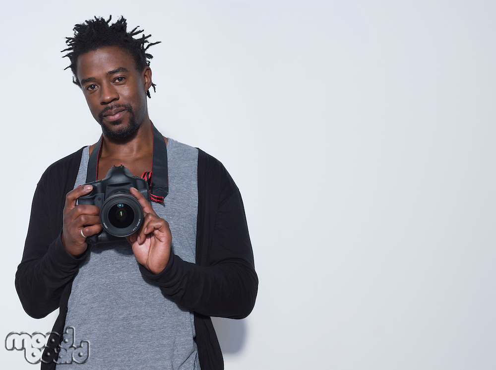 Portrait of mid adult (30-35 years) photographer holding camera studio shot