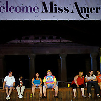 Pedestrians sit on a stage where Miss America contestants had been introduced in a ceremony that afternoon on the boardwalk in Atlantic City, NJ on September 3, 2014.  Historically the setting for the pageant, Atlantic City hosted for the first time again last year.  Economically the city is struggling, 4 casinos have already or will be closing in the near future, resulting in the loss of thousands of jobs.