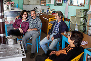 Locals with a visitor at the small shop and combined coffee bar at the little mountain village of Sklavopoula located about 20 km from the city of Paleochora on the Greek island of Crete.